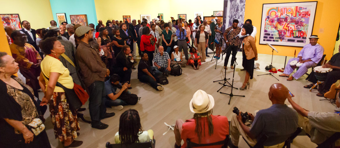 Performers and audience at community art event