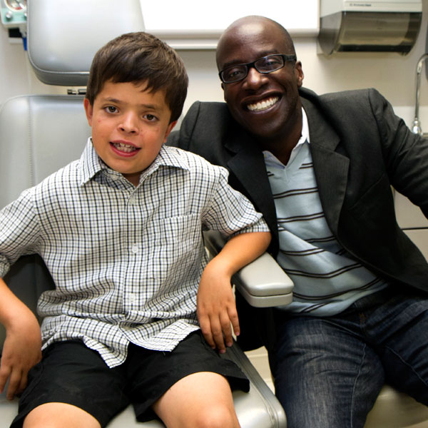 Ty with his surgeon, Russell Reid, MD, PhD, two months after the halo device was removed.