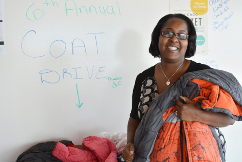LaKeesha Carter stands holding a coat donated to the drive