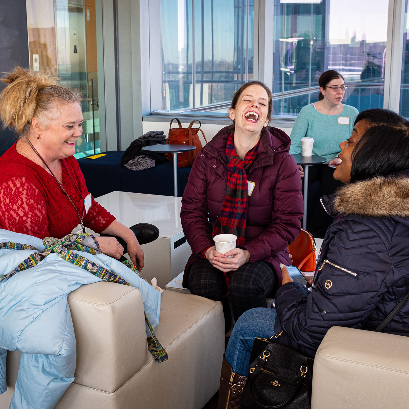 Two women wearing red talking at staff Valentine's coffee hour