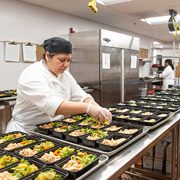 A woman in a chef's coat makes hundreds of meals