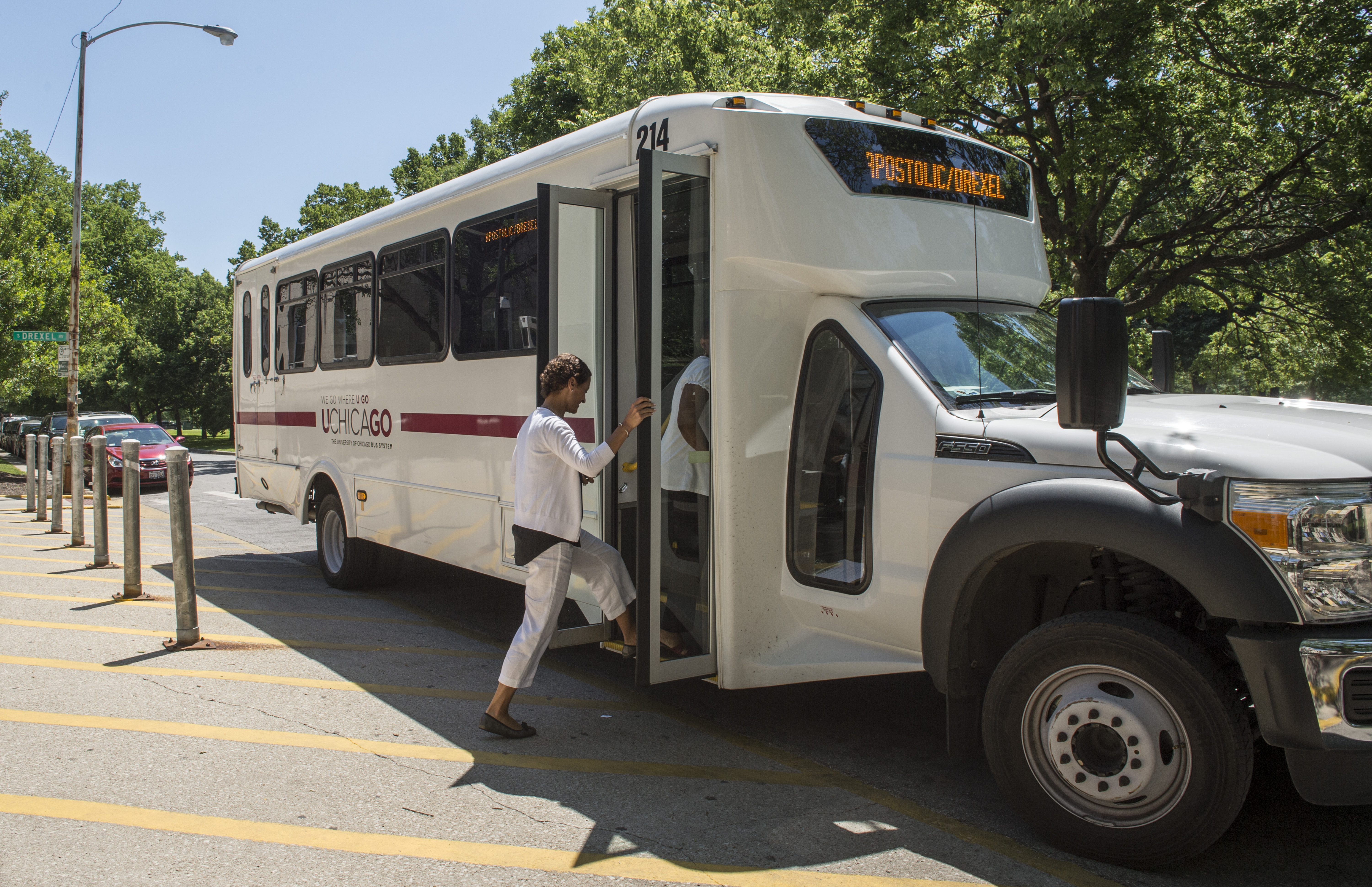 A member of the University community boards one of the UGo shuttles outside of a University of Chicago Medicine building.