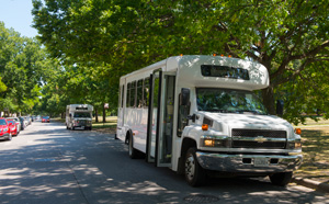 Two UGo daytime shuttles wait for passengers along the Midway Plaisance.