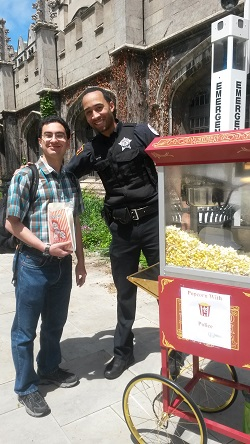 UCPD Officer Tawrence Walton and a student pose during a Popcorn with the Police event on campus.