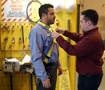 Safety staff inspecting fall protection body harness system on Facilities Services employee