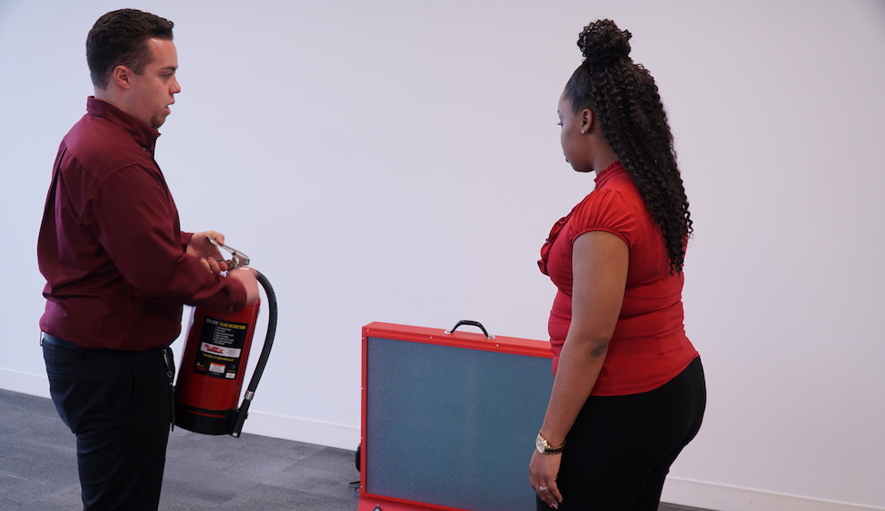 Safety staff demonstrating fire extinguisher use