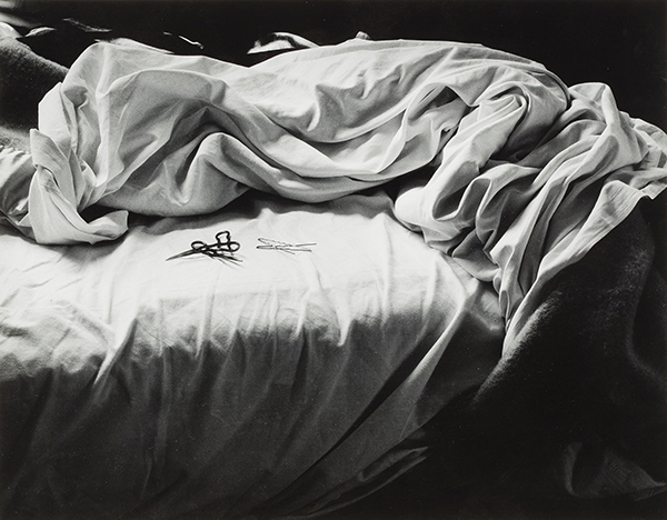 Unmade bed with rustled sheets and several hairpins resting on it, black and white photo.