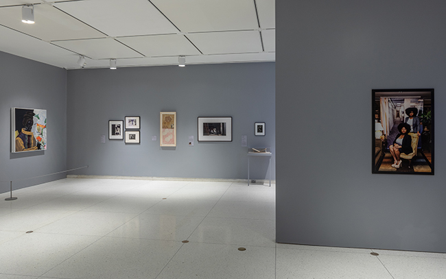 Wide-angle view of a gallery with a mix of paintings, photos, and other works.