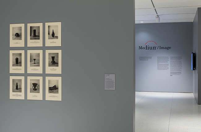 A grid of 9 prints are hung on a gray wall, on another wall in the background text reads Medium / Image