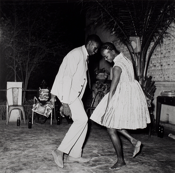A black and white photograph of two people dancing close together, their heads almost touching, the man in a suit and shoes and the woman in a dress and barefoot.