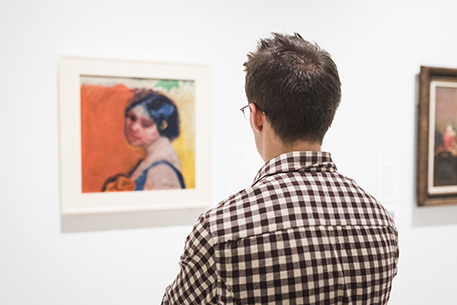 Visitor looking at Max Pechstein's painting Head of a Girl