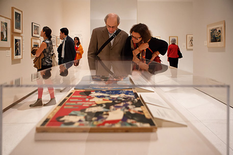 Visitors look at art in the exhibition Awash in Color
