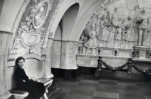 In a black-and-white photograph, a mother and her child sit in an empty subway station enveloped by walls adorned with detailed reliefs of a crowd adoring Joseph Stalin.