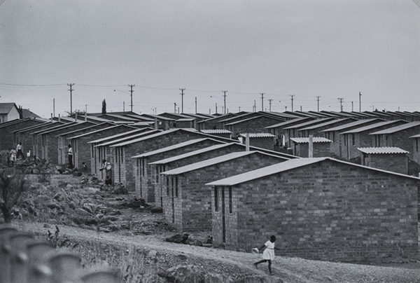 In a black-and-white photograph, a young girl runs down a road alongside a swath of blocky, uniform brick houses.