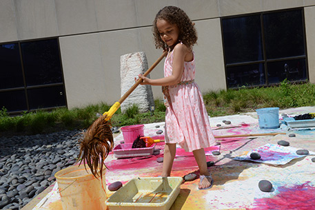 Young artists paints with a mop