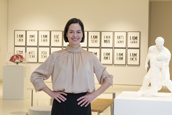 Headshot of Issa Lampe in a gallery surrounded by art