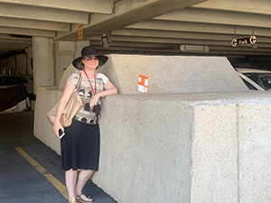 A person leans against a car encased in concrete with an orange parking ticket on it