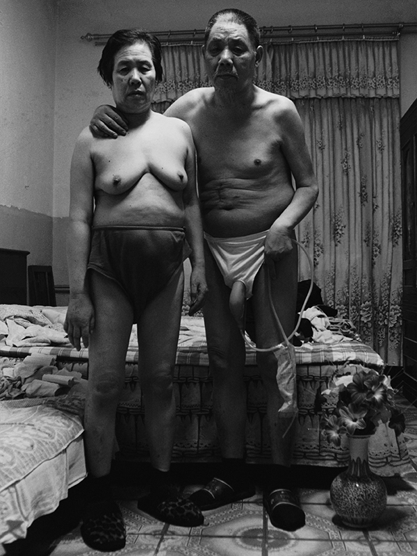 A husband and wife, stand, semi-nude in their apartment.