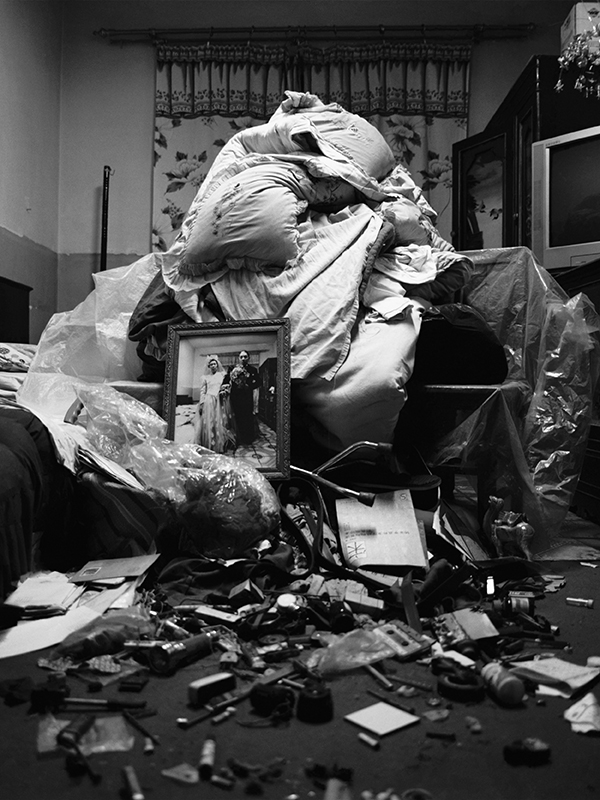 A bed piled with detritus of caregiving and healthcare and a photo of a husband and wife