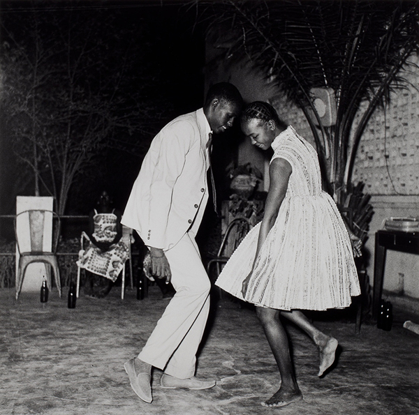 In a black-and-white photograph, a two people lean toward each other while dancing at an outdoor venue.