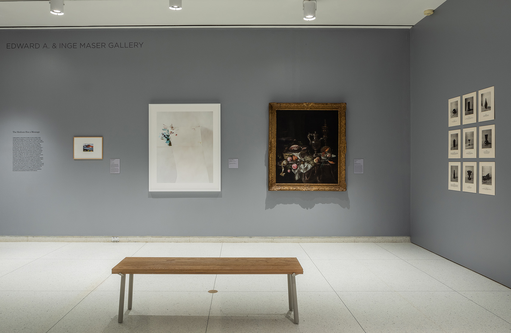 Framed photographs, a painting, and other works hang on a gray gallery wall, with a wooden bench in the foreground