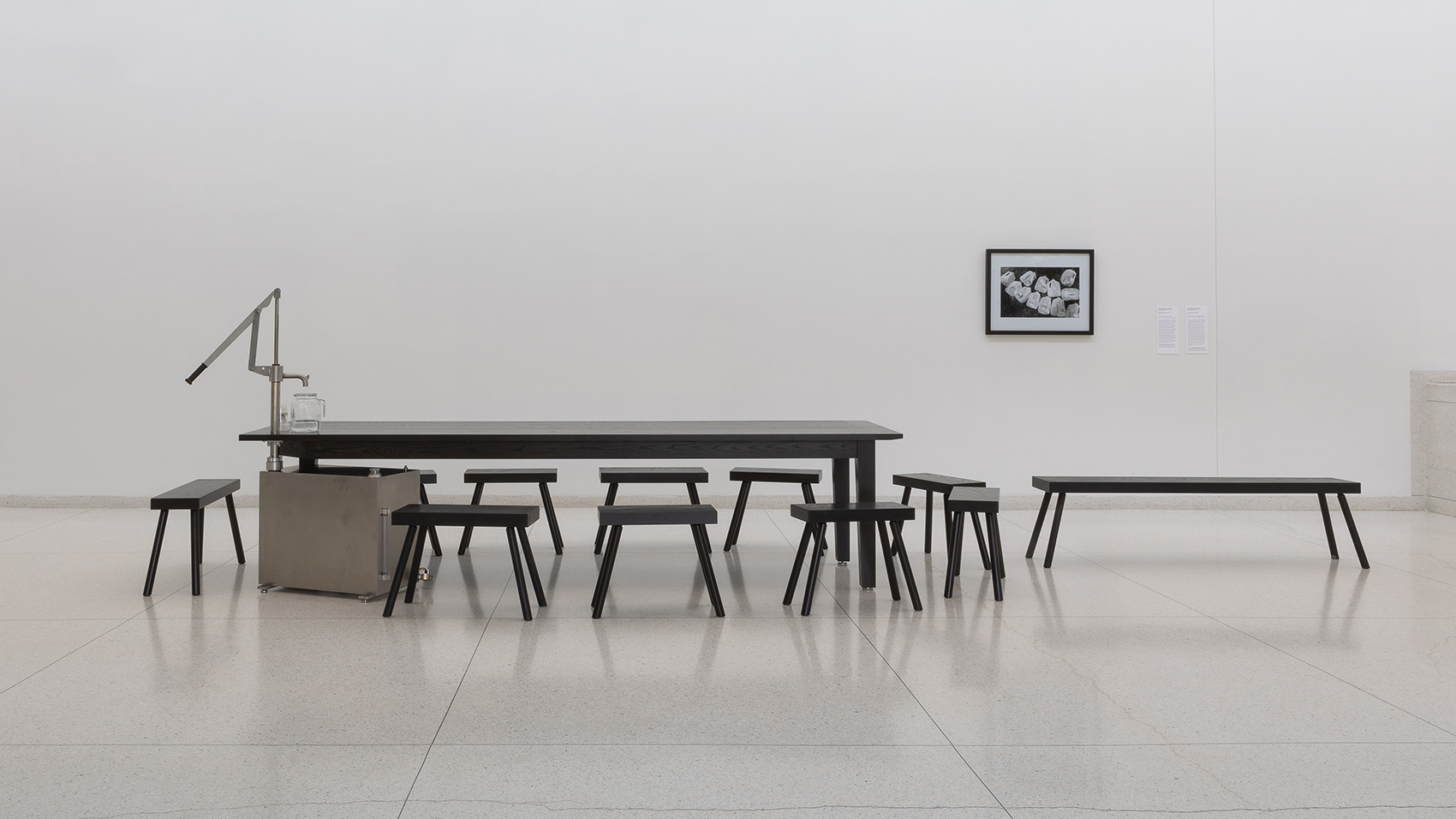 A hand pump attached to a metal canister serves as the 4th leg of a dark wooden table in a white museum gallery