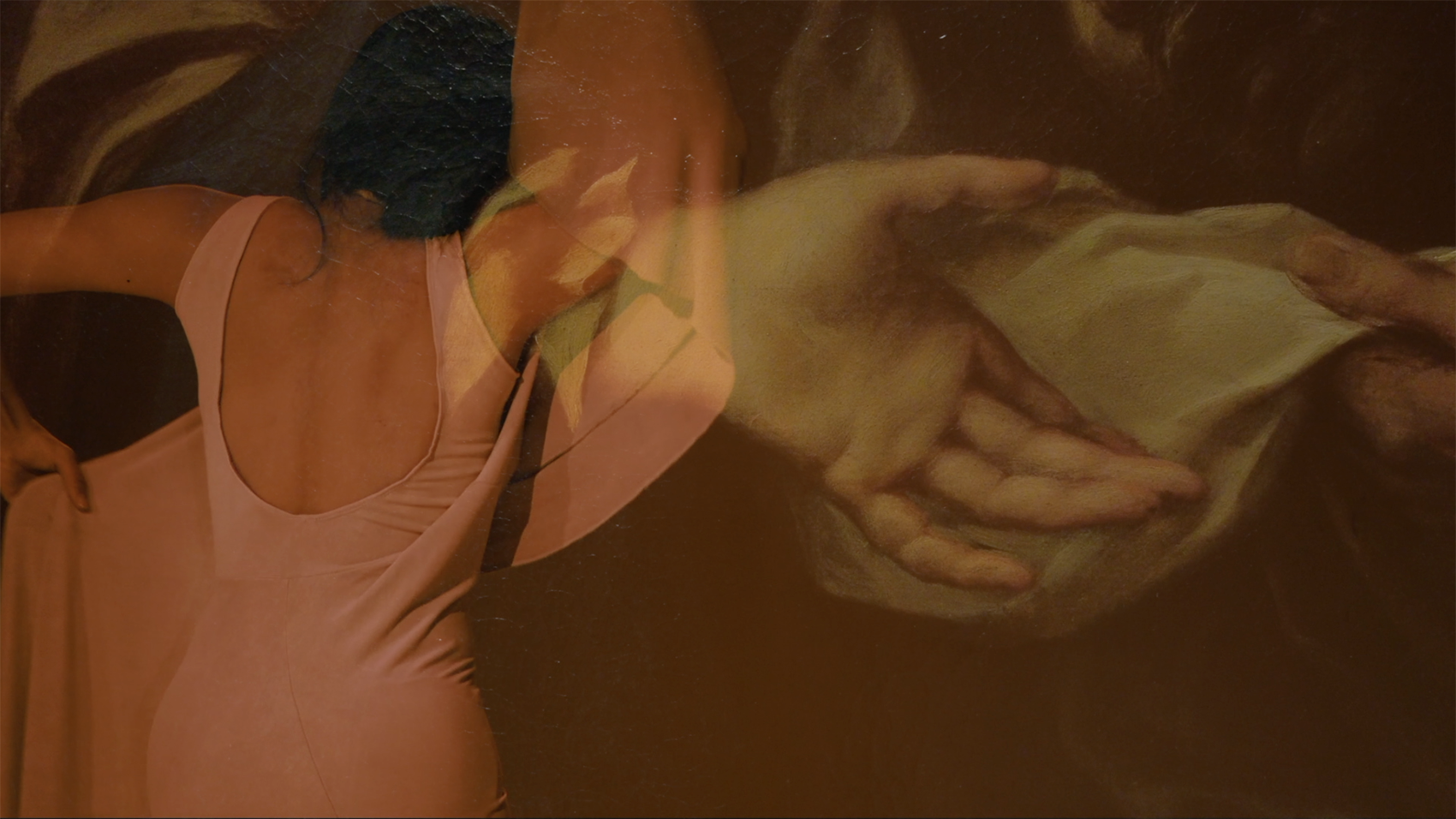 A dancer moves wrapped by a superimposed image of painting