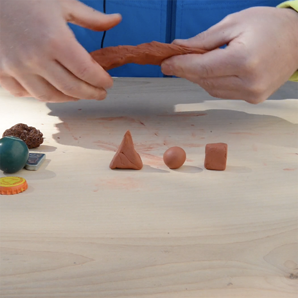 Small clay shapes—a pyramid, a sphere, a cube—sit on a wood table while a person molds clay.
