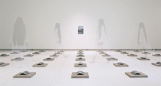 A ghostly figure walks among rows of tiles in a white gallery