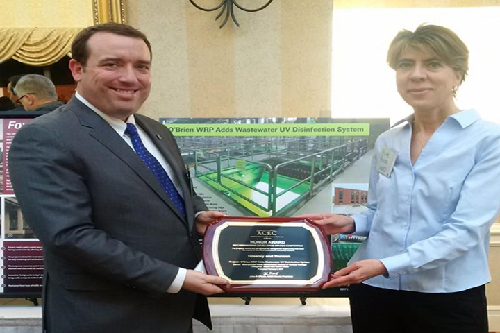 Andy Martin from Greeley & Hansen and MWRD Principal Civil Engineer Beata Busza accept the Honor Award from the American Council of Engineering Companies (ACEC) Illinois Chapter for the O'Brien Water Reclamation Plant (WRP) UV disinfection project.