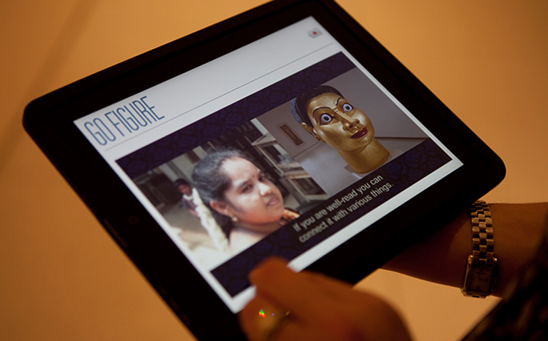 A museum visitor interacting with the Go Figure app