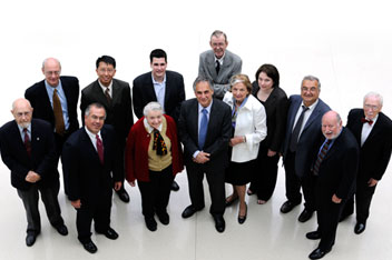 University President Robert J. Zimmer is flanked by 12 awarding-winning Chicago alumni.