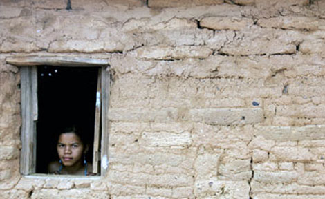 A child looks out from a window in Guaribas city, northeastern Brazil August 8, 2006. Brazil's high poverty rate is a major issue in the impoverished northeast