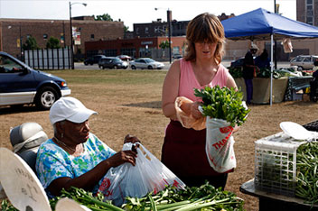 Wendy Buffington, right, helps Eldoris Charles bag her produce at the Bronzeville Market