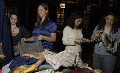 "Sarah Schwartz and Katie Henry, left, turn in scarves as Laura Pulido and Chelsea Johnson look at their craftsmanship. Johnson formed ""Commuknity,"" an RSO dedicated to knitting, in response to the many student knitting circles on campus."