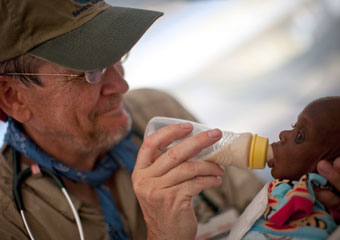 Richard Cook, an anesthesiologist at the Medical Center, gives treatment to a malnourished Haitian infant whose mother died during the earthquake.