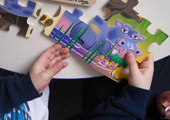 A child assembles a jigsaw puzzle