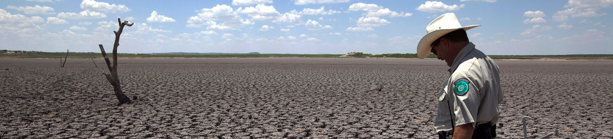 A ranger examines a drought-cracked landscape