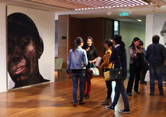 Guests view Xu Weixin's realist paintings of miners at exhibit.