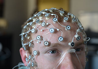 UChicago doctoral student Aaron Ball shows how a high-density EEG net is worn during a demonstration.
