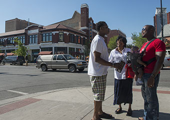 Friends Bryant Mclemore-Smith, left, and Makali Robinson, holding his daughter Nila, 6-mos., along with Robinson's mother-in-law Patricia Jordan, stop to chat at 53rd Street and S. Harper in Chicago's Hyde Park neighborhood.