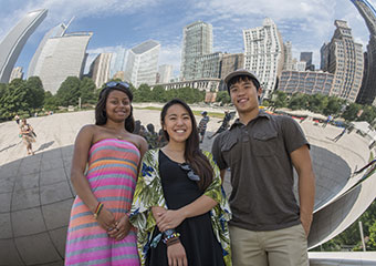 "From left: UChicago Promise first year students Kayla Moore, from Morgan Park High School; Sara Kuse, from Northside College Prep; and Warren Mui, from Kenwood Academy, with the city skyline reflected behind them in ""Cloud Gate,"" also known as The Bean, a"