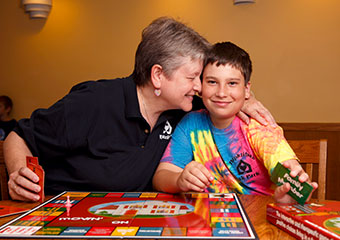 With her 14-year-old great-nephew, Henry Krause, Davida Williams plays Movin' On, a board game she created to help children in group homes learn life skills.