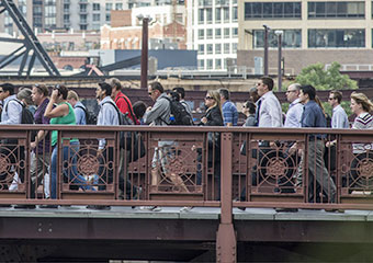 Downtown Chicago commuters make their way across the Madison Street bridge.