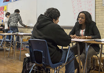 Match tutor Miriam Kamya works with a student at Edwin G. Foreman High School in Chicago.