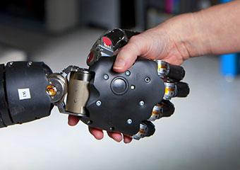 Robotic hand shakes human hand