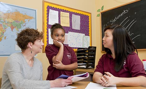 Grace Seol Bechle (right) and her field instructor Elizabeth Brown speak to a third-grader from the North Kenwood-Oakland Campus