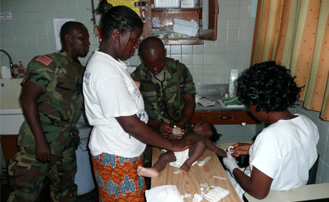 Liberian army medics and nursing staff work in the emergency department at John F. Kennedy Hospital attempt to gain IV access on an infant with malaria.