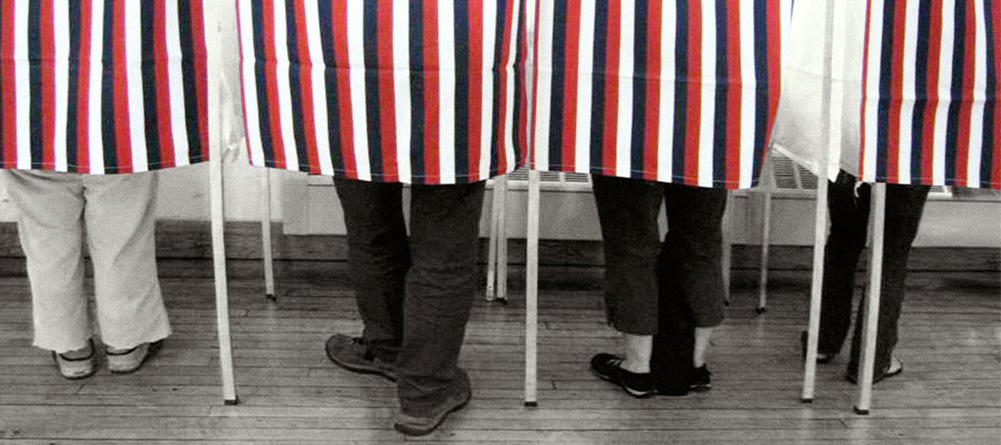 Photo of voters in an old voting booth.